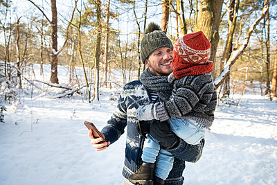 Father carrying son while holding smart phone in forest during winter - p300m2281827 by Frank van Delft