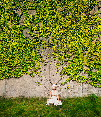 Portrait serene woman meditating at wall overgrown with ivy - p301m2075519 by Sven Hagolani