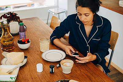 Woman checking blood sugar level while having breakfast on table at home - p426m1537128 by Maskot