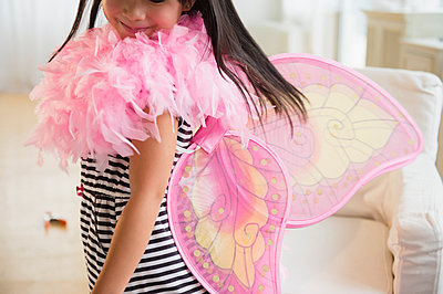 Filipino girl playing dress-up in living room - p555m1415575 by JGI/Jamie Grill