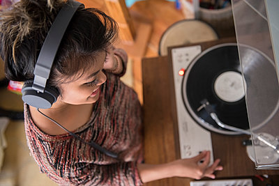 Mixed Race woman listening to record player with headphones - p555m1444108 by JGI/Jamie Grill