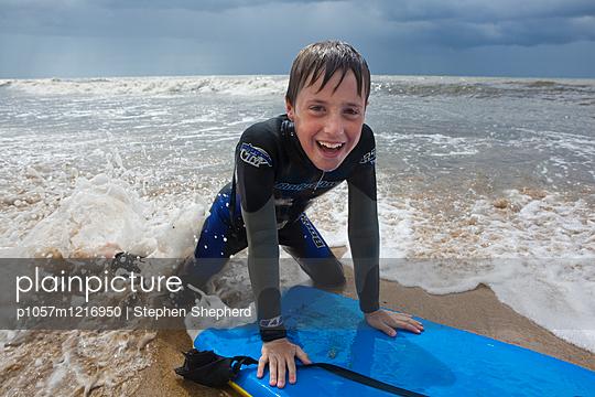 Junge mit Schwimmbrett am Strand - p1057m1216950 von Stephen Shepherd