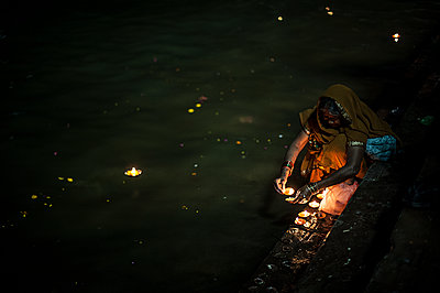 Woman lighting candle near the river - p1007m1144415 by Tilby Vattard