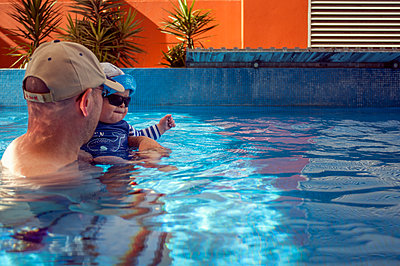Father and young son in an open air swimming pool - p1047m1492566 by Sally Mundy