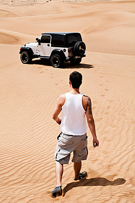 Man walking back to his Jeep in a desert - p1515m2107639 by Daniel K.B. Schmidt