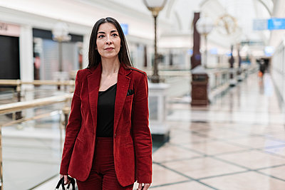 Confident mature businesswoman in red blazer walking at subway station - p300m2265911 by COROIMAGE