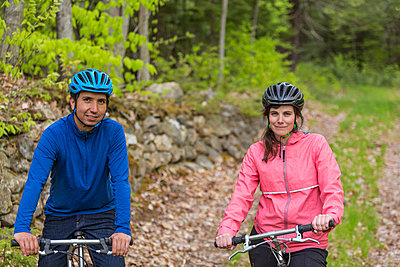 A couple mountain biking on a forest trail near Stonehouse Pond in Barrington, New Hampshire. - p343m1443419 by Jerry Monkman