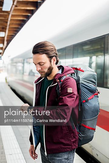 Mann am Bahnsteig schaut auf die Uhr - p1114m1159746 von Carina Wendland