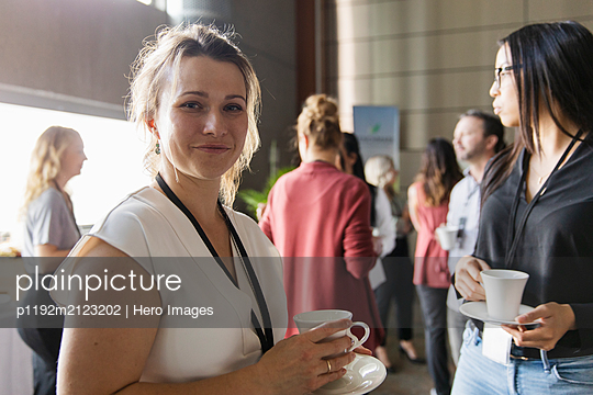 Portrait confident businesswoman networking during conference coffee break - p1192m2123202 by Hero Images