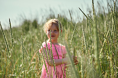 Adorable little girl among grass in Iceland - p1166m2130736 by Cavan Images