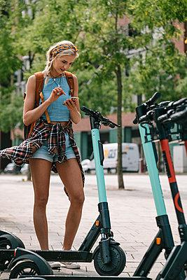 Junge Frau unterwegs mit dem E-Scooter - p299m2108615 von Silke Heyer