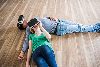 Young couple lying on floor in empty apartment wearing VR glasses - p300m1459718 by Uwe Umstätter