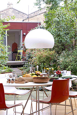 White pendant light hangs over garden table set with fruit and bread - p349m790618 by Polly Eltes