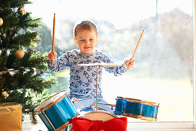 Boy playing toy drum kit on christmas day - p429m1227343 by Peter Muller
