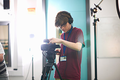Young male college student filming in TV studio - p429m1494627 by Peter Muller