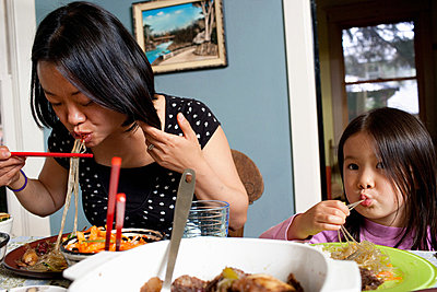 Mother and daughter eating meal - p9240861 by Charles Gullung