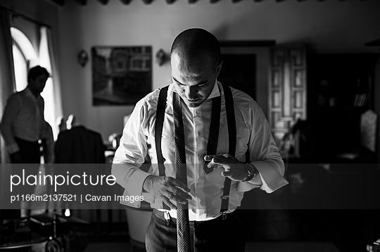 Groom adjusting his tie for wedding - p1166m2137521 by Cavan Images