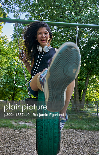 Portrait of happy young woman on a swing - p300m1587440 von Benjamin Egerland