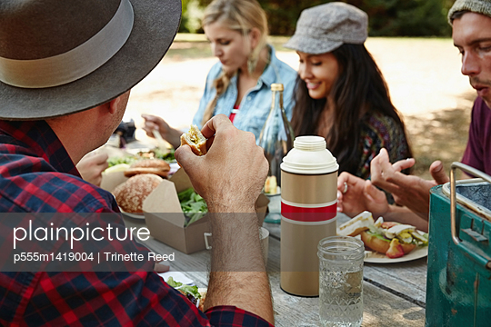 Friends eating at picnic bench in park