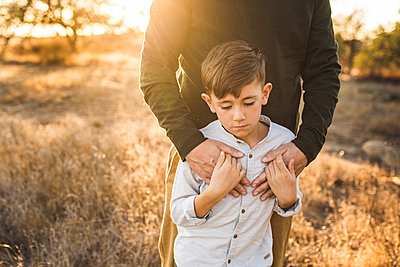 Close up of young boy being embraced by father in California field - p1166m2073616 by Cavan Images