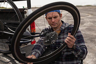 Disabled man in a wheelchair taking bike out of a car - p1315m2162381 by Wavebreak