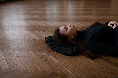 Young woman lies on the parquet floor day dreaming - p1646m2231466 by Slava Chistyakov