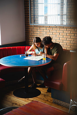 Young couple sitting at table in a cafe with map - p300m2042810 von Michela Ravasio