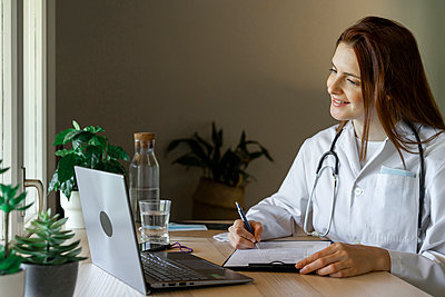 Young female doctor writing medical report during online consultation from home office - p300m2224881 by VITTA GALLERY