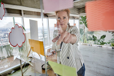 Businesswoman sticking adhesive notes on glass wall at office - p300m2265227 by Jo Kirchherr