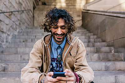 Cheerful man using mobile phone while sitting on steps - p300m2276747 by Xavier Lorenzo