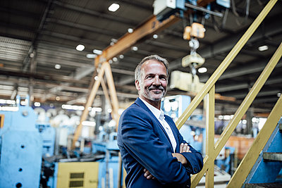 Male professional with arms crossed standing in steel mill - p300m2299250 by Gustafsson