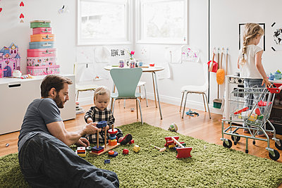 Father and daughters playing with toys in playroom at home - p426m1451761 by Maskot