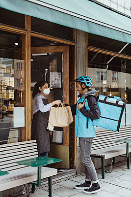 Smiling delivery man collecting order from sales woman at deli store during pandemic - p426m2270640 by Maskot