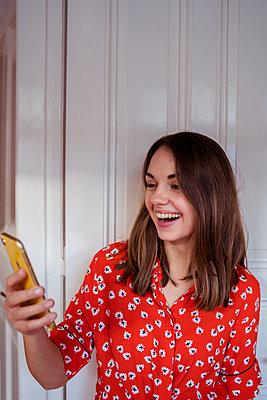Junge Frau lacht ins Handy - p432m2148044 von mia takahara