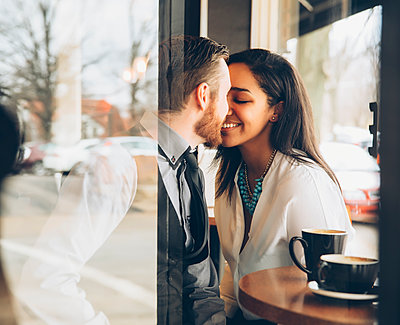 Smiling couple kissing in cafe - p555m1408572 by Inti St Clair photography