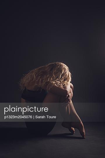 Sitting woman hiding her face - p1323m2045076 von Sarah Toure