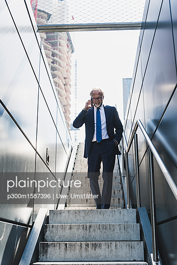 Smiling mature businessman on staircase in the city on cell phone - p300m1587396 von Uwe Umstätter