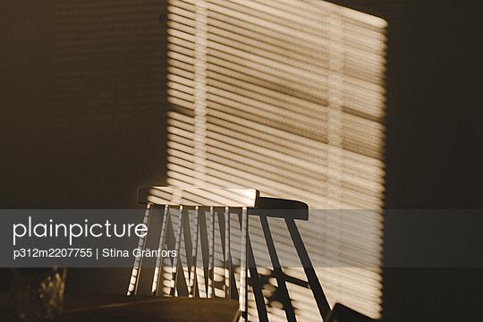 Shadow made by window shutter on wall - p312m2207755 by Stina Gränfors
