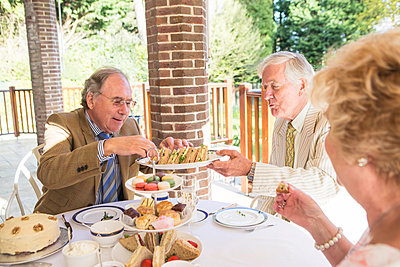 Senior people having tea on the balcony - p1026m1164201 by Patrick Frost