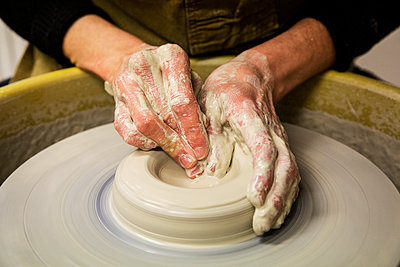 Close up of potter wearing apron working on pottery wheel, shaping clay vase. - p1100m1575700 by Mint Images