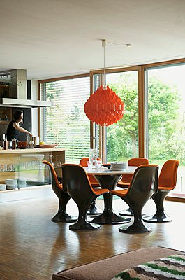 Brown plastic shell chairs with orange cushions in dining area below orange pendant lamp - p1183m995996 by Heinze, Winfried