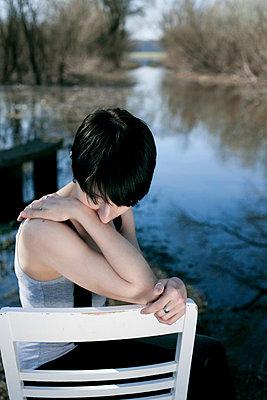 Frau auf Stuhl vor Wasser - p1220m1051368 von Schall & Schnabel
