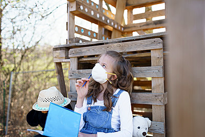 pretty young girl with mouth protective mask is sitting in the garden in front of a tree house writes something in her blue notebook, diary during the corona quarantine, lower austria - p300m2180245 von Epiximages