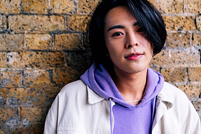 Young man wearing purple hooded shirt in front of brick wall - p300m2293313 by Angel Santana Garcia