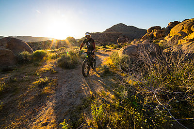 Man riding mountain bike on dirt track  - p343m1475628 by Cavan Images