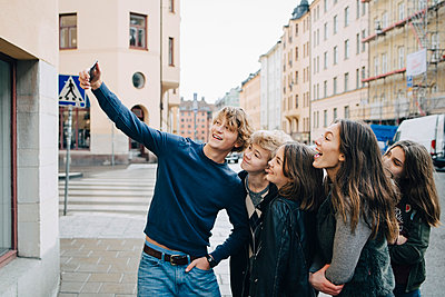 Male taking selfie with friends through smart phone while standing in city - p426m1555964 by Maskot