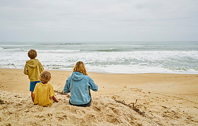 Family on beach looking away at sea, Florianopolis, Santa Catarina, Brazil, South America - p429m1519607 by Stephen Lux