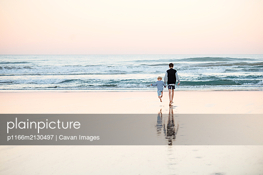 Teen boy holding little brother's hand on beach - p1166m2130497 by Cavan Images
