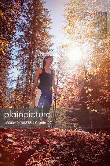 Woman jogging in autumn forest, stretching for warm up - p300m2166373 von Studio 27