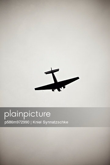 Blick auf ein Propellerflugzeug am grauen Himmel - p586m972990 von Kniel Synnatzschke